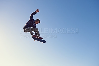 Buy stock photo A young man doing tricks on his skateboard at the skate park