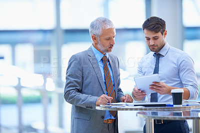 Buy stock photo Shot of a young businessman with a tablet discussing work with his colleague