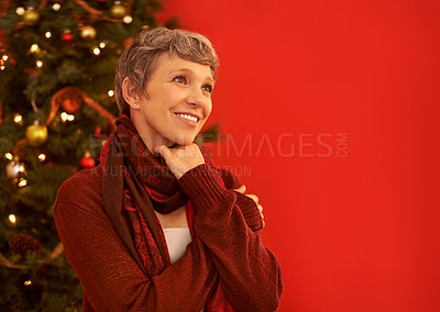 Buy stock photo A happy mature woman looking thoughtful in front of a Christmas tree