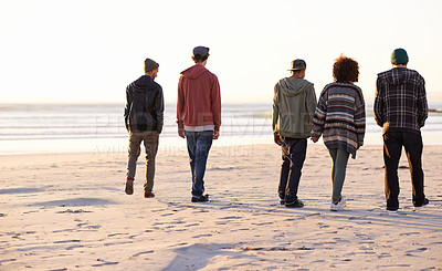 Buy stock photo Shot of a group of friends walking along a beach at sunset