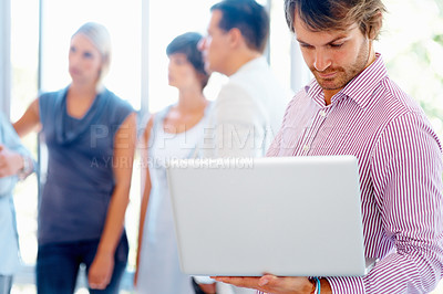 Buy stock photo Young business man working on laptop with team in blur background