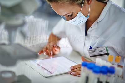 Buy stock photo A young researcher recording her results on a tablet in t he lab