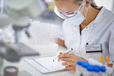 Buy stock photo A young researcher recording her findings on a tablet in the lab