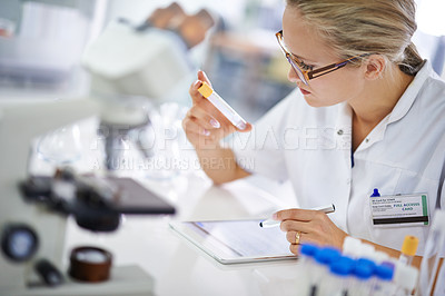 Buy stock photo A young scientist recording her findings on a tablet