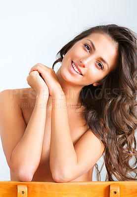 Buy stock photo Portrait of a beautiful young woman sitting backwards on a chair