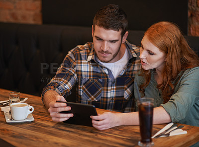 Buy stock photo Shot of a young couple using a digital tablet while on a date at a restaurant
