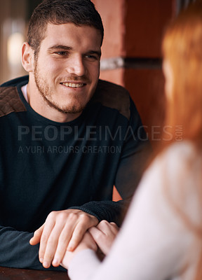 Buy stock photo Shot of an attractive young man smiling at his girlfriend while on a date