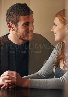 Buy stock photo Cropped shot of an affectionate couple holding hands while on a date