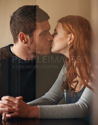 Buy stock photo Shot of an affectionate young couple sharing a kiss while on a date