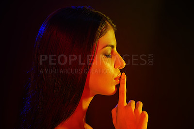 Buy stock photo Studio shot of a beautiful young woman with her finger on her lips in artistic lighting