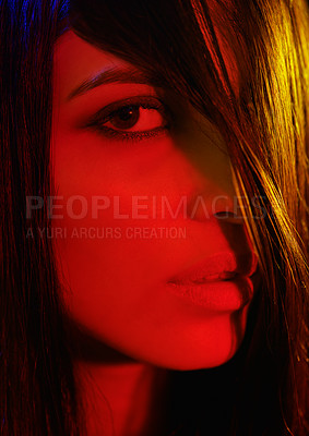 Buy stock photo Studio portrait of a beautiful young woman with artistic lighting