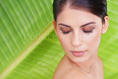 Buy stock photo Studio shot of a beautiful young woman with her eyes closed posing in front of a leaf