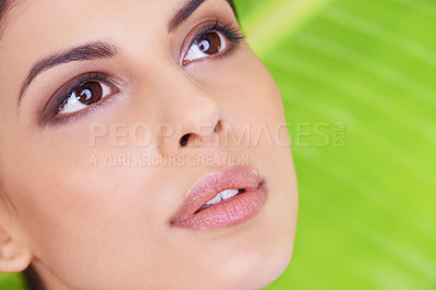 Buy stock photo Studio shot of a beautiful young woman posing in front of a leaf