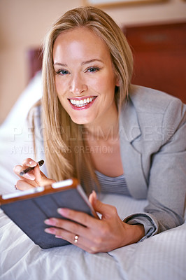 Buy stock photo A young businesswoman using a digital tablet in a bedroom