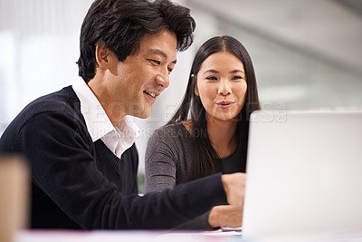 Buy stock photo Shot of two business colleagues working together at a laptop in the office