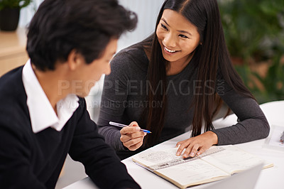 Buy stock photo Shot of two business colleagues having a friendly discussion while working together