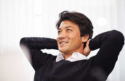 Buy stock photo A relaxed businessman sitting with his hands behind his head at his desk