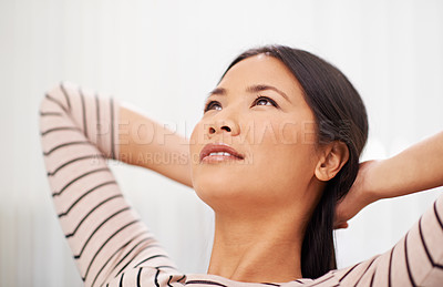 Buy stock photo Shot of an attractive asian businesswoman leaning back with her arms behind her head