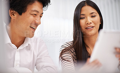 Buy stock photo Cropped shot of two business colleagues discussing work on a tablet
