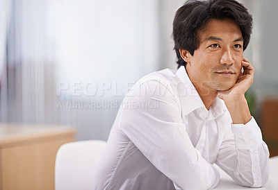 Buy stock photo Shot of a handsome asian businessman looking thoughtful while sitting at his desk