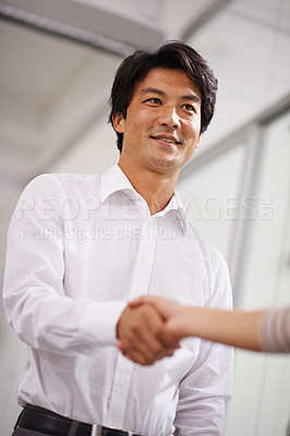 Buy stock photo Shot of a handsome asian businessman shaking hands with another person