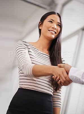 Buy stock photo Shot of a young asian businesswoman shaking hands with another person