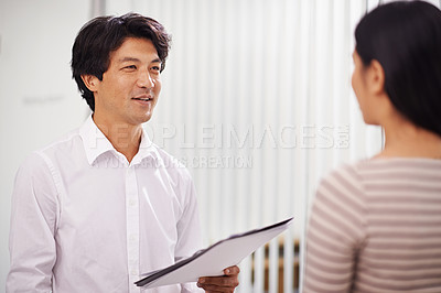 Buy stock photo Shot of two business professionals discussing work in the office
