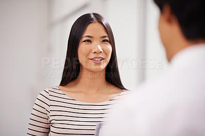 Buy stock photo A young asian office worker speaking to a colleague