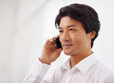 Buy stock photo Shot of a handsome asian businessman using his mobile phone in the office