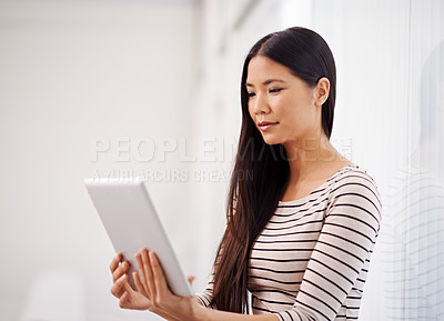Buy stock photo An attractive young asian businesswoman using a digital tablet in the office