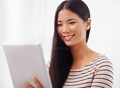 Buy stock photo Shot of a young asian businesswoman using a digital tablet in the office