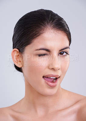 Buy stock photo Studio shot of a beautiful young woman winking against a gray background