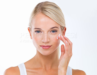 Buy stock photo A beautiful young woman applying moisturiser to her face