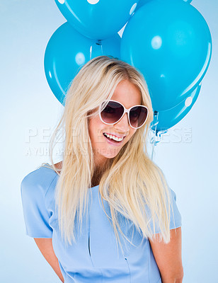Buy stock photo A beautiful young woman in sunglasses posing with balloons