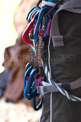 Buy stock photo Shot of the ccarabiners attached to a female rock climber