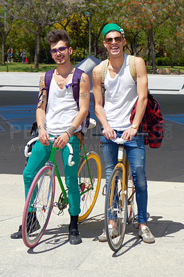 Buy stock photo Full length shot of two young guys sitting on their bikes outdoors