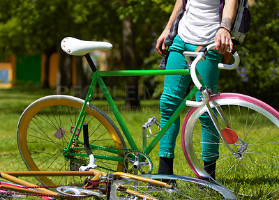 Buy stock photo Cropped shot of a young guy standing next to his bike outdoors