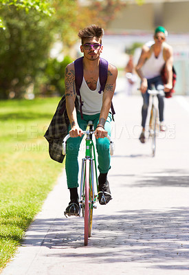 Buy stock photo Full length shot of two young guys cycling outdoors