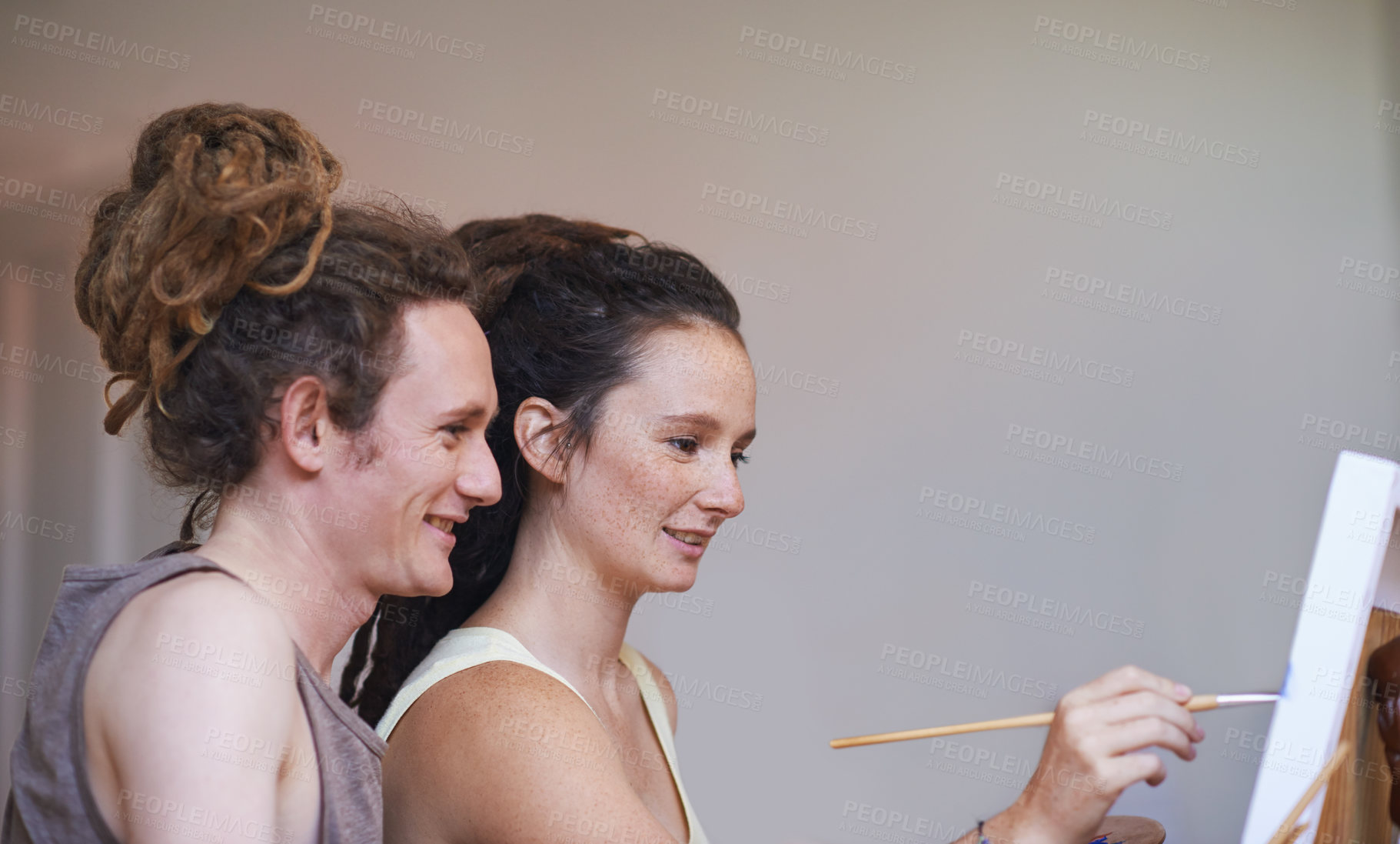 Buy stock photo A cropped view of a young artist painting with her boyfriend's support