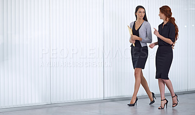 Buy stock photo Two colleagues walking together in the office while have a conversation