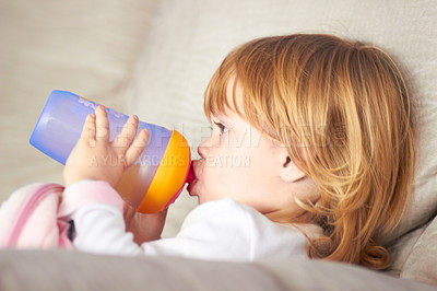 Buy stock photo Shot of an adorable little girl drinking from a sippy cup