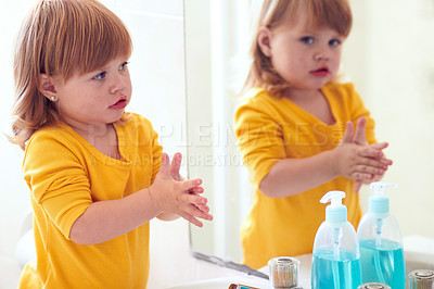 Buy stock photo Shot of a little girl looking in the mirror as she washes her hands