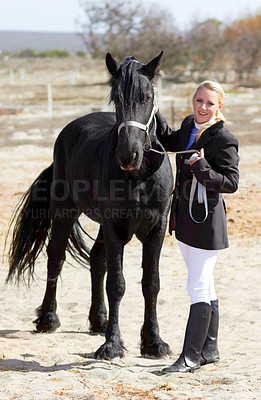 Buy stock photo Shot of a beautiful young woman standing next to her horse