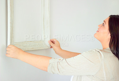 Buy stock photo Shot of an attractive woman hanging up a mirror in her home