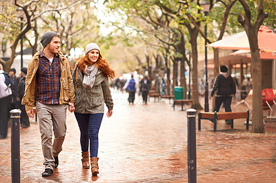 Buy stock photo Shot of a happy young couple walking through an urban area together