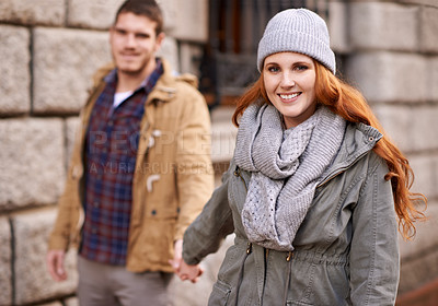 Buy stock photo Portrait of a happy young couple walking through an urban area together