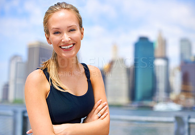 Buy stock photo Portrait of a beautiful young woman standing beside a river while out for a run in the city