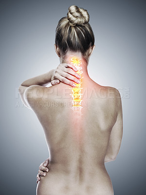 Buy stock photo Rearview shot of a woman holding her back in pain