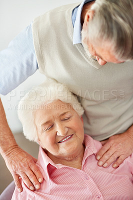 Buy stock photo Shot of a husband lovingly massaging his senior wife's shoulders