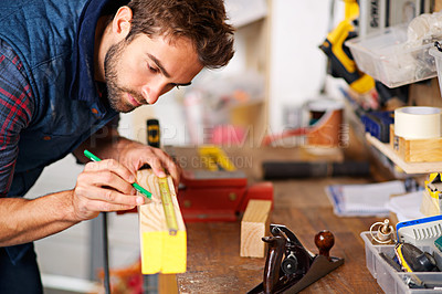 Buy stock photo Shot of a handsome young carpenter measuring a piece of wood